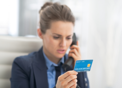 Photo of a woman doing a credit card transaction over the phone